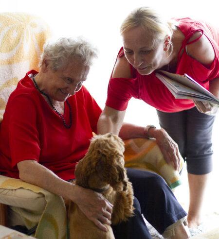 Frau Anna mit Pflegerin Eva und Therapiehund Roxi